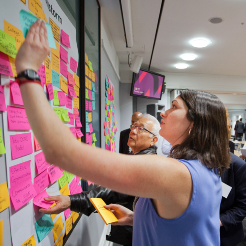 A woman reviews sticky notes on a wall at the London meeting